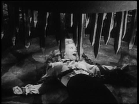 1947 B/W MS Woman (Betty Hutton) screaming for help while tied to platform and struggling as spikes are lowered upon her / California, USA