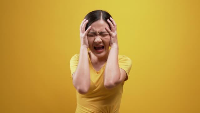 woman screaming over isolated yellow background - plain background stock videos & royalty-free footage