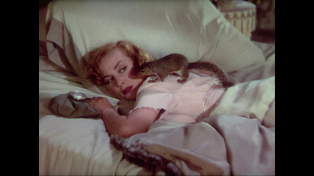 1937 woman (carole lombard) screams after realizing she has a squirrel on her back - hysteria stock videos & royalty-free footage