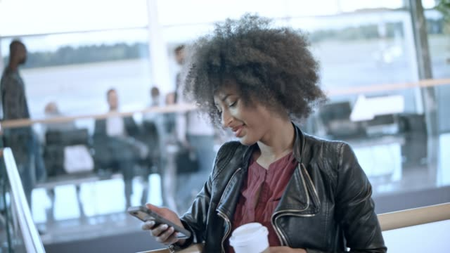 woman scrolling her phone while drinking coffee and waiting for her flight at the airport - big hair stock videos & royalty-free footage
