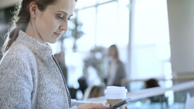 vídeos de stock e filmes b-roll de woman scrolling her smartphone while drinking coffee at the airport - copo descartável