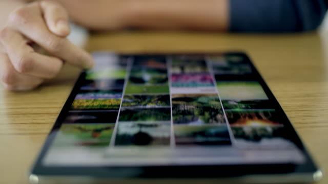 cu woman scrolling through photos on digital tablet - scrolling stock videos & royalty-free footage