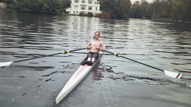 woman sculling rowboat in river - sculling stock videos & royalty-free footage