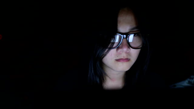 Woman search internet on laptop in the dark