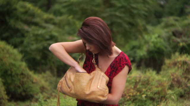 hd dolly: woman searches for something in her purse - purse stock videos & royalty-free footage