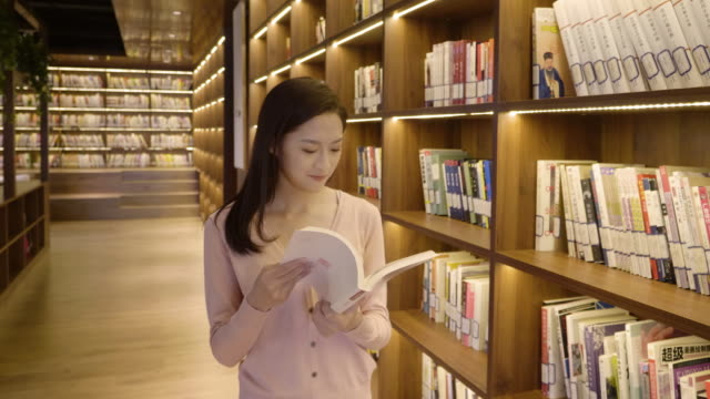 vídeos de stock e filmes b-roll de ds ms woman searching for books in library, beijing, china - escolher