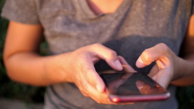 vidéos et rushes de femme recherchant avec le téléphone mobile dans le parc - symbole
