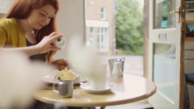 日当たりの良いカフェで食事を調味料の女性 - 玉子点の映像素材/bロール