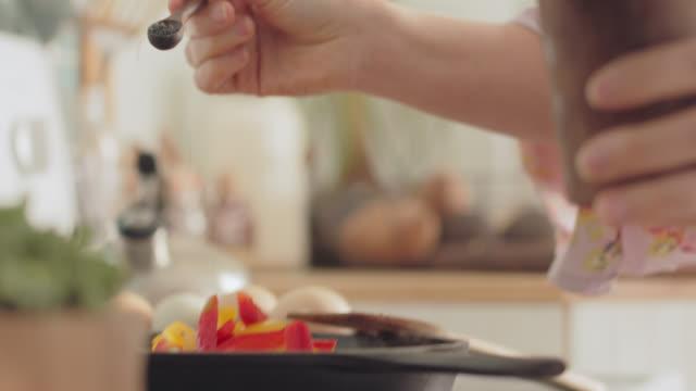 cu woman seasons peppers cooking in a pan - sprinkling stock videos & royalty-free footage