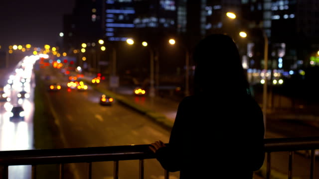 woman see the city standing on bridge at night - introspection stock videos & royalty-free footage