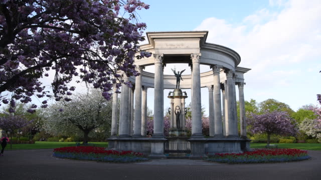 a woman seen running past the welsh national war memorial in alexandra gardens in cathays park in cardiff wales uk - joggerin stock-videos und b-roll-filmmaterial