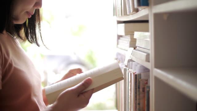 女性は本棚の本を選び、図書館で読書をする - absence点の映像素材/bロール