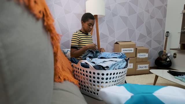vídeos y material grabado en eventos de stock de mujer que selecciona ropa en la sala de estar para la donación. - sólo mujeres jóvenes