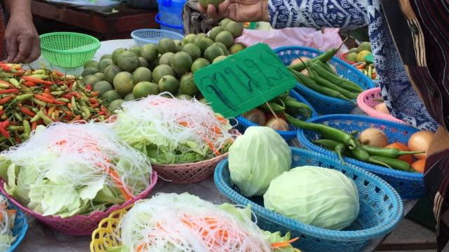 タイのストリート マーケットでライムを選択する女性
