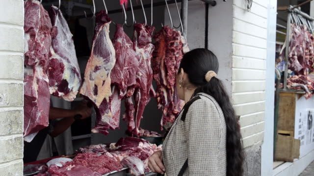 MS Woman selecting pieces of meat for purchase at shop / Otavalo, Ecuador