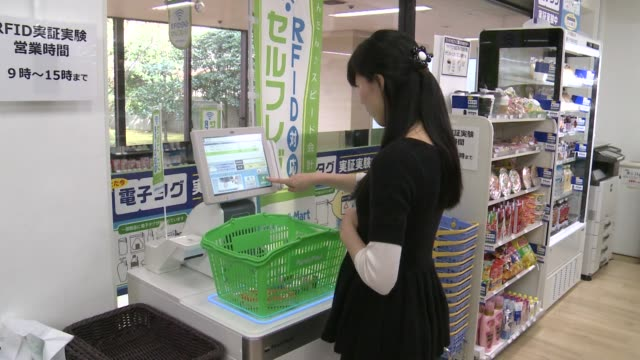 a woman selects items from a shelf during a demonstration of an unmanned cash register at a familymart uny holdings co familymart convenience store... - 支払い点の映像素材/bロール