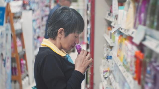 frau wählt produkt in den regalen im laden,close-up - shampoo stock-videos und b-roll-filmmaterial