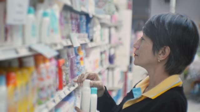 vídeos de stock, filmes e b-roll de a mulher seleciona o produto nas prateleiras na loja, close-up - cosmético
