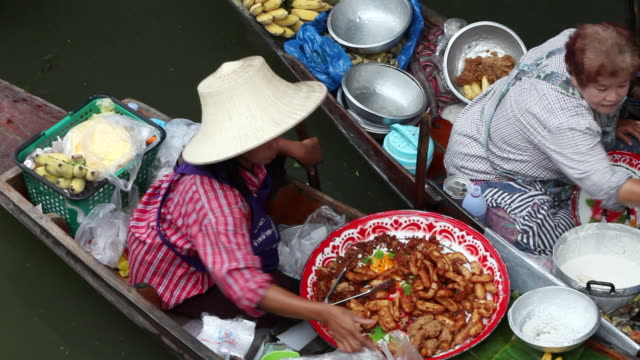 MS Woman  selling delicious food out of her boat at   Damnoen Saduak Floating Market  / Bangkok, Ratchaburi Provinvr, Thailand