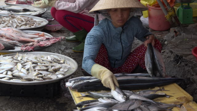 Woman selling fish at street market