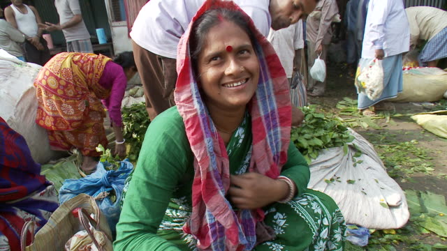 stockvideo's en b-roll-footage met a woman selling flowers at a market smiles. - calcutta