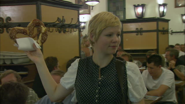 ms pan woman selling pretzels in hofbrauhaus, munich, bavaria, germany - german culture stock videos & royalty-free footage