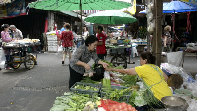Woman selling vegetables at street market