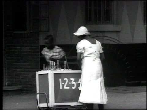 1939 B/W Woman sells ice cream to girl, pedestrian walking down Harlem street / New York City