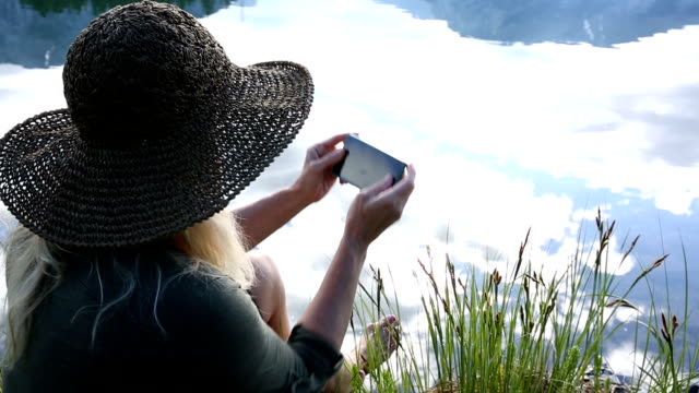 Woman sends text from smart phone, by lake