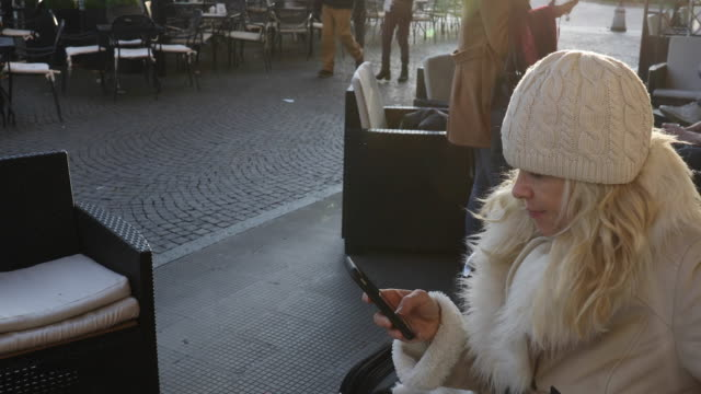 woman sends text in busy cafe piazza - woolly hat stock videos & royalty-free footage