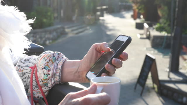 woman sends text while drinking macchiato - cafe macchiato stock videos and b-roll footage