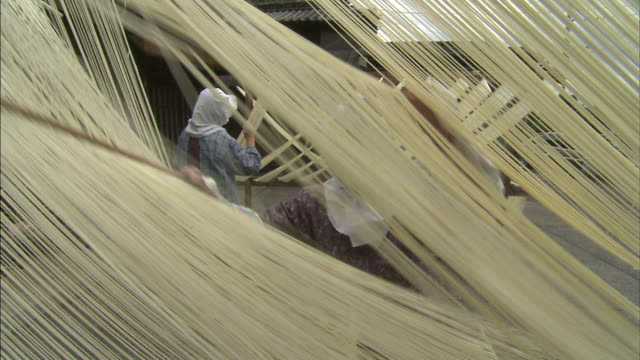 A woman separates somen noodles for drying.