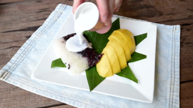 woman serve sticky rice with mango and pouring coconut milk - sticky stock videos and b-roll footage