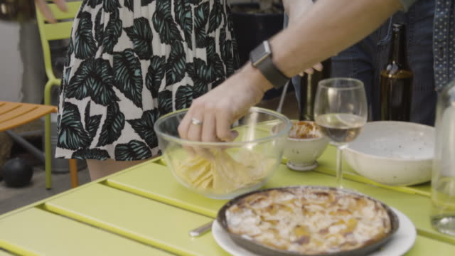 Woman serves bowl of crisps, friends snack on food, chatting and laughing.