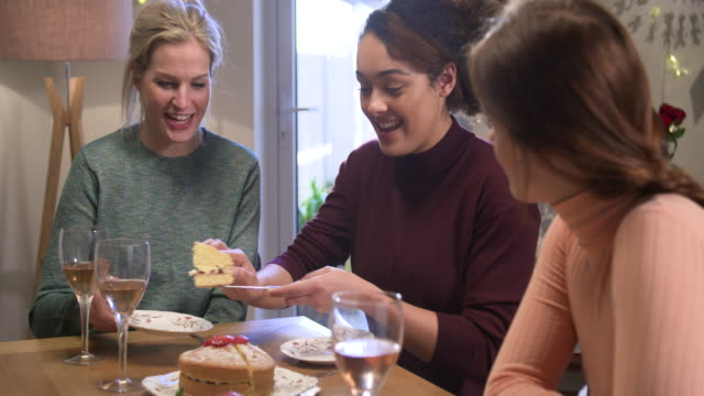 Woman serves cake to friends around the table.
