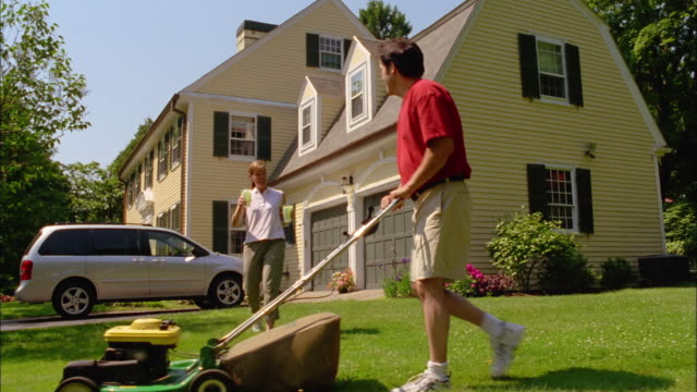 a woman serves lemonade to a man mowing the lawn. - lawn mower stock videos and b-roll footage