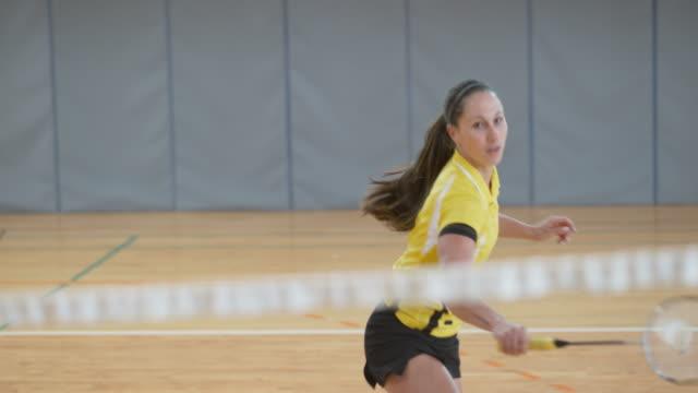 vídeos de stock, filmes e b-roll de mulher servindo e jogando badminton indoor - badmínton esporte