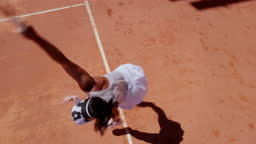 Woman serving ball during tennis match on clay court