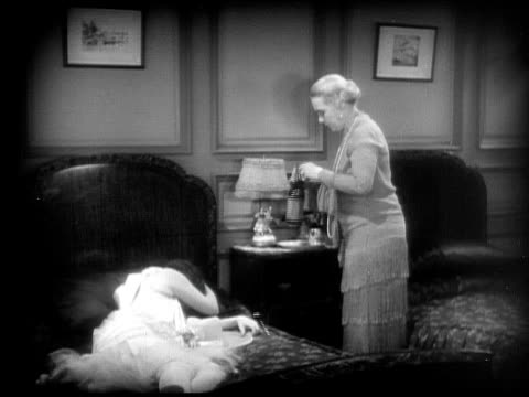 cu, ms, b&w, woman serving beverage to other woman lying on bed, 1920's  - anno 1928 video stock e b–roll