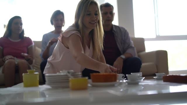 vidéos et rushes de femme de service de pause de café pour les visiteurs - famille nombreuse