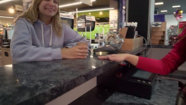 カフェでコスチューマーにコーヒーを出す女性 - 使い捨て製品点の映像素材/bロール