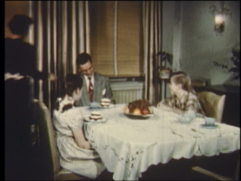 1950 woman serving family at dinner table with tray of desserts - 1950 stock-videos und b-roll-filmmaterial