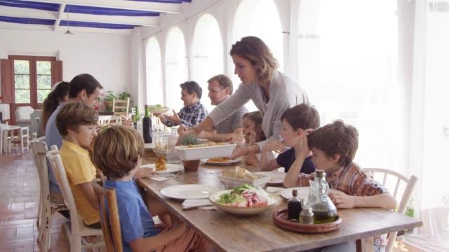 vidéos et rushes de femme servant la nourriture aux enfants à la table à manger - famille multi générations