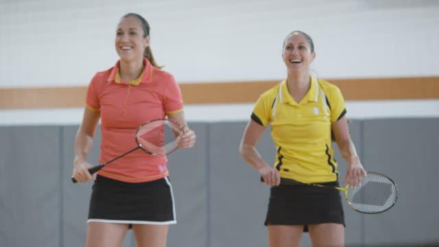 vídeos de stock, filmes e b-roll de dobra a mulher servindo em jogar badminton indoor - badmínton esporte