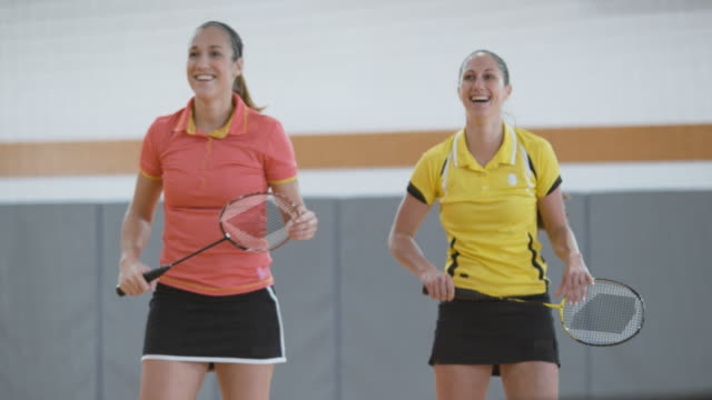 Woman serving in playing doubles indoor badminton