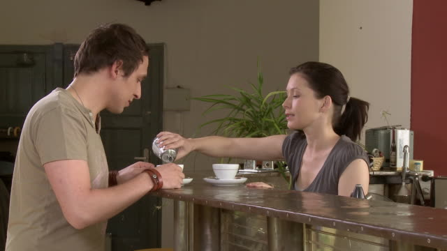 ms woman serving man coffee at kitchen counter, then they drink and talk face to face / berlin, germany - coffee drink stock videos & royalty-free footage
