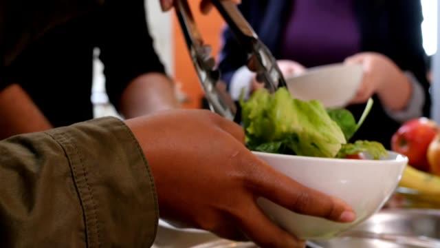 Vrouw die diende voor salade naar diverse groep van vrienden tijdens diner