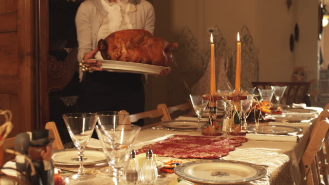 vídeos de stock e filmes b-roll de ms woman serving turkey at decorated thanksgiving table / lehi, utah, usa - lehi