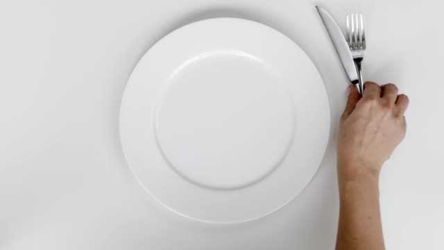 woman setting up table, a plate and cutlery for meal - dining table stock videos & royalty-free footage