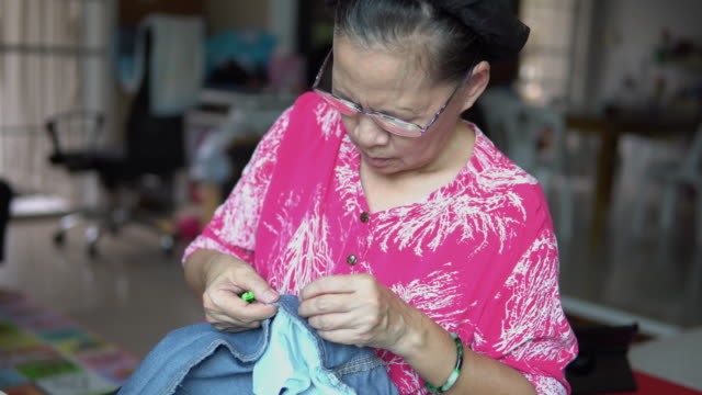 woman sewing a cloth at home. - customised stock videos & royalty-free footage